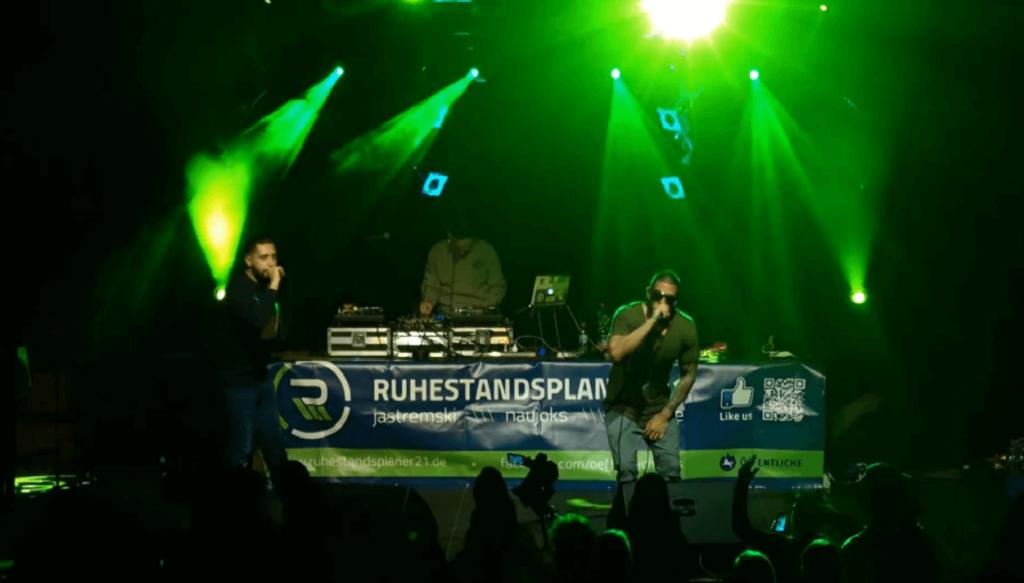 das bild zeigt einen ausschnitt eines liveauftritts zwei künstler stehen auf der bühne und rappen